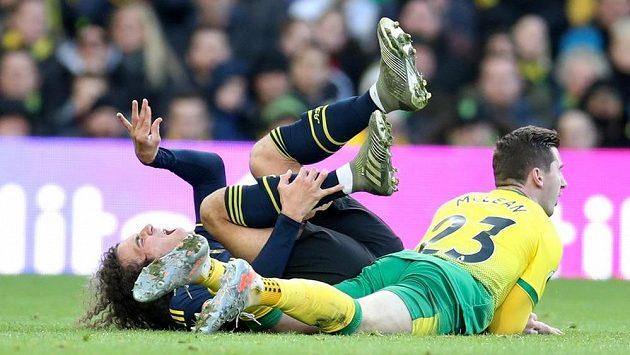 V pozici vleže se na trávníku ocitli Matteo Guendouzi (vlevo) z Arsenalu a Kenny McLean z Norwiche.