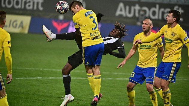 Zlínský stoper hlavičkuje míč před útočníkem Českých Budějovic Fortune Basseym.