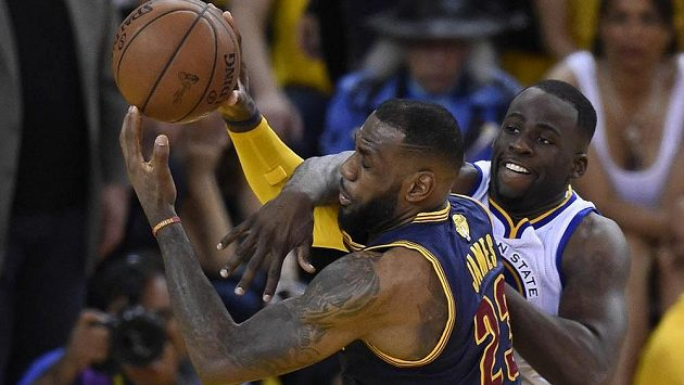 Hvězda Clevelandu LeBron James (vlevo) je atakován Draymondem Greenem z Golden State Warriors.
