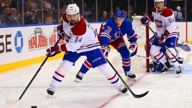 Český hokejový útočník Tomáš Plekanec se snaží přihrát puk v utkání s týmem New York Rangers v NHL. Zabránit mu chce v rozehrávce obránce Rangers Brady Skjei.