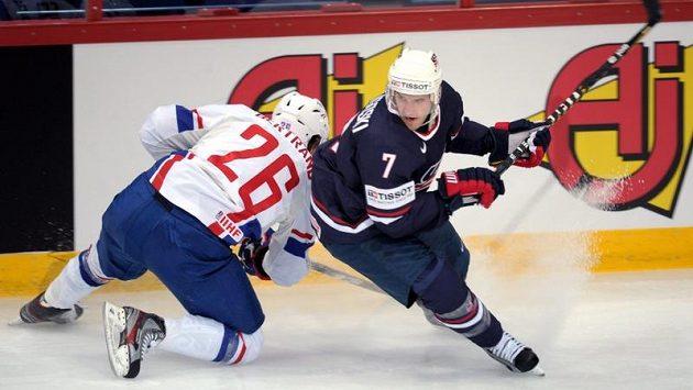 Francouz Charles Bertrand (vlevo) se snaží zastavit Alexe Goligoskiho z USA v úvodním utkání MS v hokeji.