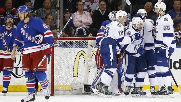 Centr Tampy Bay Lightning Tyler Johnson (vpravo uprostřed) přijímá gratulace od svých spoluhráčů, zatímco hráči NY Rangers odjíždí se sklopenou hlavou.