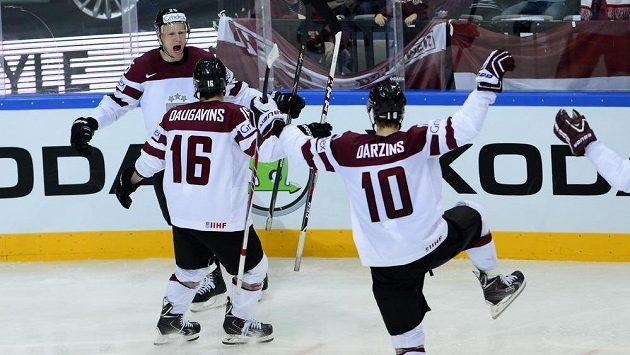 Lotyšští hokejisté (zleva) Andris Dzerins, Kaspars Daugavins a Lauris Darzins se radují z gólu proti Švýcarsku.