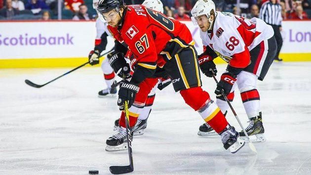 Michael Frolík z Calgary kontroluje puk před obránci Ottawy.