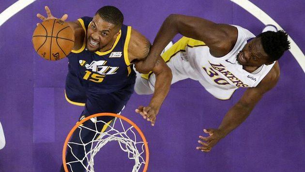 Derrick Favors (vlevo) z Utahu Jazz doskakuje míč před vlastním košem. Brání ho Julius Randle z Los Angeles Lakers.