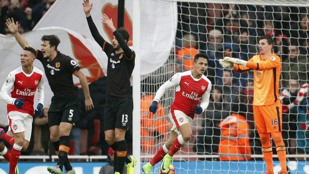 Alexis Sánchez slaví vedoucí gól Arsenalu v utkání Premier League s Hullem. Jeho hráči gestikulují, že střelec zahrál rukou, ale jejich protesty byly marné. Sudí gól uznal.