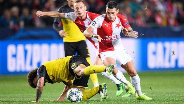 Axel Witsel z Dortmundu kouzlí na zemi s míčem a dotírající Nicolae Stanciu ze Slavie Praha během utkání základní skupiny Ligy mistrů v Praze.