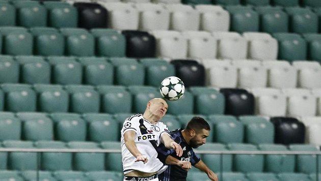 Dani Carvajal z Realu Madrid (vpravo) v hlavičkovém souboji s obráncem Legie Adamem Hlouškem na prázdném varšavském stadiónu..