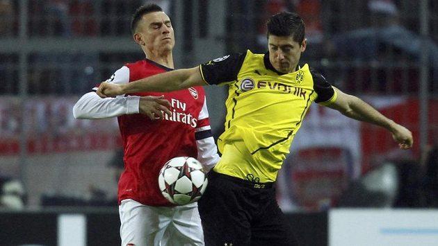 Útočník Borussie Dortmund Robert Lewandowski (ve žlutém) bojuje o míč se zadákem Arsenalu Laurentem Koscielnym.