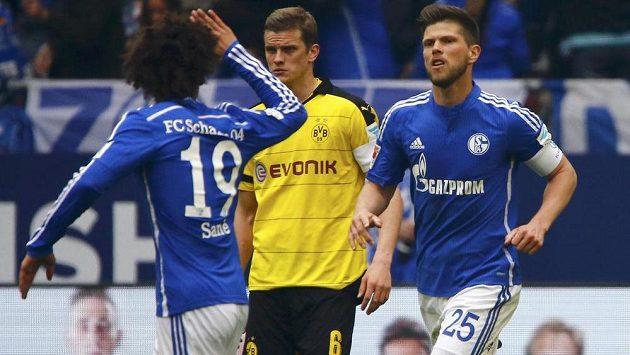 Útočník Schalke Klaas-Jan Huntelaar (vpravo) slaví se spoluhráčem Leroyem Sanem vyrovnávací gól proti Dortmundu. Uprostřed přihlíží obránce Borussie Sven Bender.