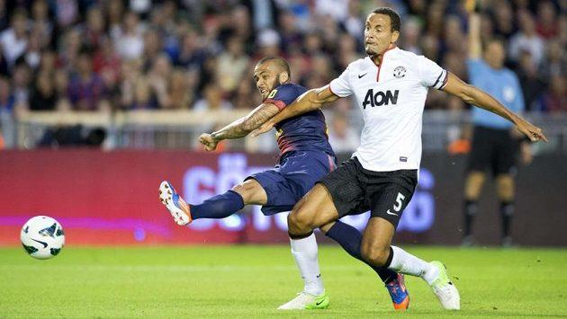 Fotbalista Manchesteru United Rio Ferdinand (vpravo) bojuje o míč s barcelonským Dani Alvesem v přátelském utkání.