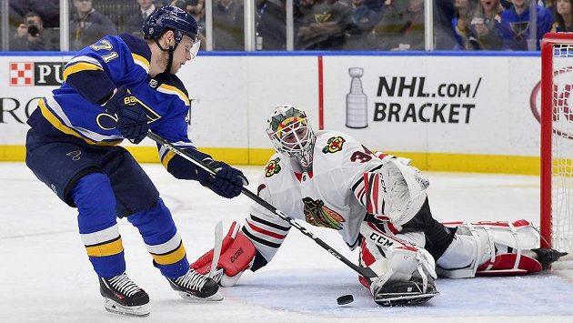 Gólman Chicaga Blackhawks J-F Berube (34) likviduje šance útočníka St. Louis Blues Vladimíra Sobotky v utkání NHL.