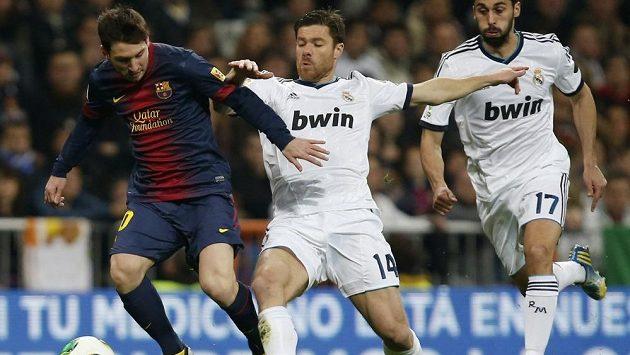 Unikajícího dirigenta Barcelony Lionela Messiho se snaží zastavit Xabi Alonso z Realu Madrid (uprostřed). Zcela vpravo je Álvaro Arbeloa.