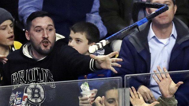 Fanoušek Bostonu chytá hokejku, kterou vhodil do hlediště útočník Bruins David Pastrňák poté, co překonal krajana v brance Detroitu Petra Mrázka.
