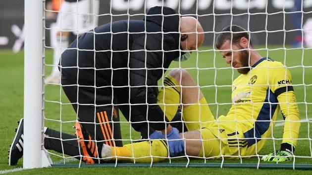 Lékař Manchesteru United se sklání nad zraněným brankářem Davidem de Geou.