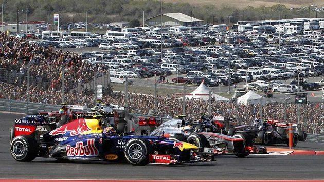 Mark Webber s vozem Red Bull (vpředu) bojuje v první zatáčce na okruhu v Austinu s Lewisem Hamiltonem z McLarenu.