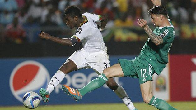 Asamoah Gyan z Ghany (vlevo) střílí gól přes alžírského obránce Carla Menjaniho.