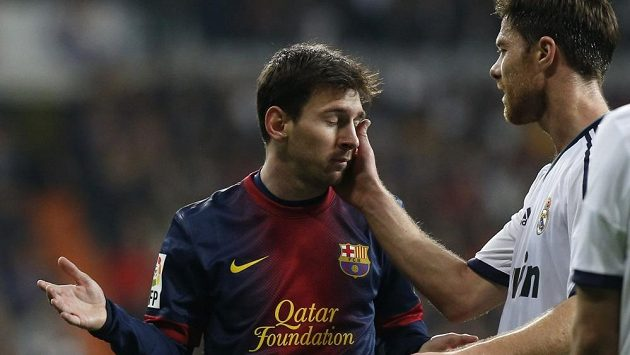 Xabi Alonso z Realu (vpravo) umravňuje sarkastickým pohlazením Lionela Messiho z Barcelony.