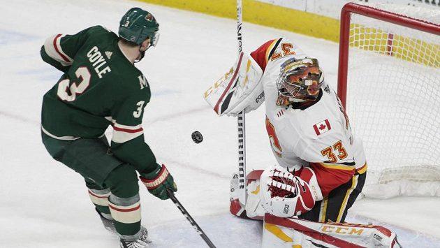 Charlie Coyle Z Minnesoty střílí na českého brankáře Davida Rittica z Calgary v utkání NHL.