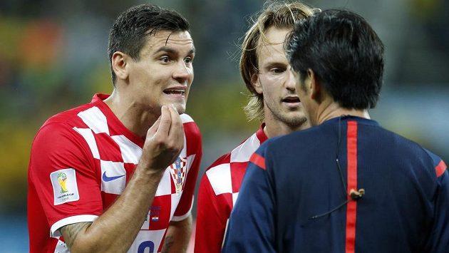 Chorvatští fotbalisté Dejan Lovren (vlevo) a Ivan Rakitič diskutují s japonským sudím Juičim Nišimurou.