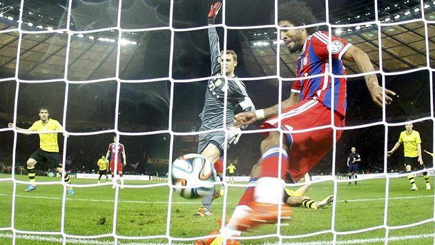 Dante z Bayernu Mnichov odkopává míč po hlavičce Matse Hummelse z Borussie Dortmund ve finále Německého poháru.