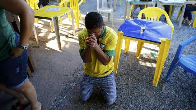 Modlící se fanoušek Brazílie během osmifinálového duelu MS s Chile.