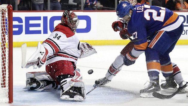 Český gólman Caroliny Petr Mrázek zasahuje proti Andersi Leemu (vlevo) v utkání 2. kola play off NHL proti NY Islanders.