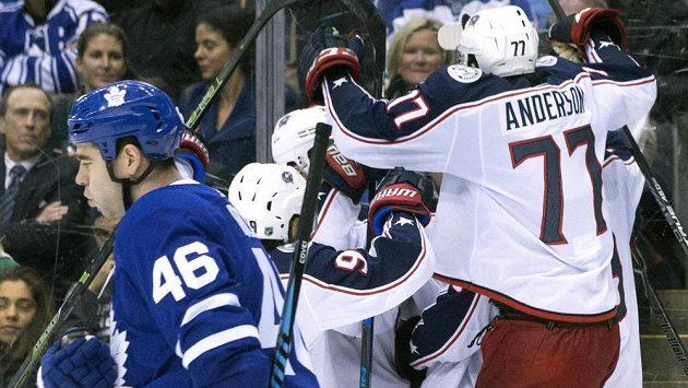 Gólová radost hokejistů Columbusu, vlevo odjíždí zklamaný obránce Toronta Roman Polák.