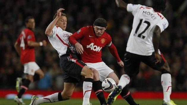 Útočník Manchesteru Wayne Rooney (uprostřed) v péči liverpoolských hráčů Lucase (vlevo) a Victora Mosese.