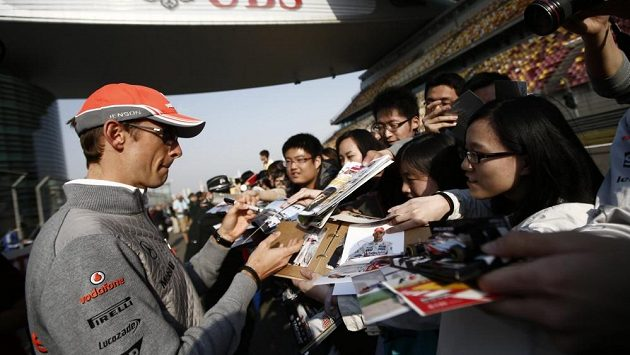Pilot McLarenu Jenson Button se podepisuje fanouškům na okruhu v Šanghaji.
