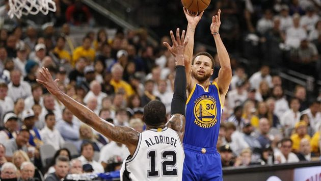 Hvězda Golden State Stephen Curry střílí přes LaMarcuse Aldridge ve třetím utkání finále Západní konference NBA.