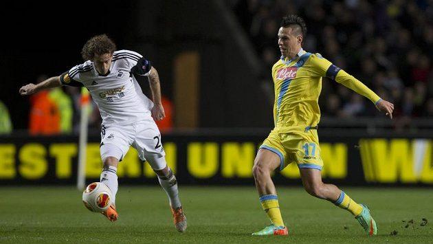 Dwight Tiendalli (vlevo) ze Swansea odkopává míč před Markem Hamšíkem z Neapole v utkání Evropské ligy.