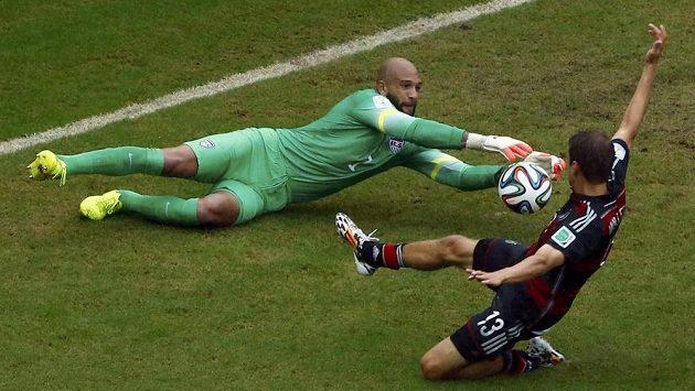 Brankář Tim Howard sbírá míč těsně před kopačkou německého útočníka Thomase Müllera.