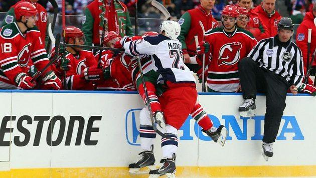 Ryan McDonagh (na ledě v bílém dresu) posílá na střídačku New Jersey útočníka Devils Travise Zajaca.
