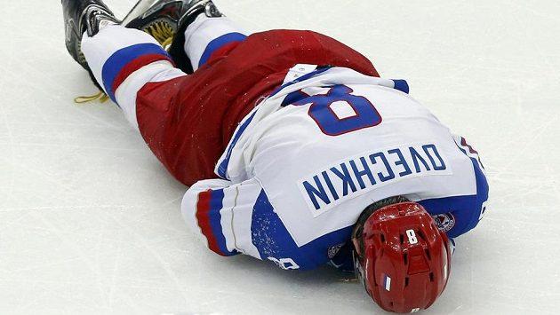 Zraněná ruská hvězda Alexandr Ovečkin leží po střetu s Němcem Marcusem Kinkem na ledové ploše.