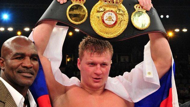 Alexandr Povětkin s pásem pro mistra světa organizace WBA. Vlevo boxerská legenda Evander Holyfield.