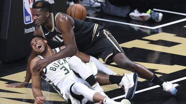 Centr basketbalistů Atlanty Hawks Clint Capela (nahoře) a hvězda Milwaukee Bucks Janis Adetokunbo padají k zemi po souboji v NBA.