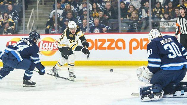 Český hokejista Bostonu David Pastrňák (v bílém) střílí na gólmana Laurenta Brossoita z Winnipegu během utkání NHL.