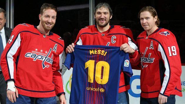 Hokejový útočník Alexandr Ovečkin pózuje s dresem Lionela Messiho. Vlevo je obránce Washingtonu Brooks Orpik, vpravo útočník Nicklas Bäckström.