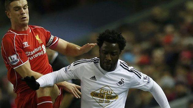 Bony Wilfried (vpravo) v dresu Swansea bojuje o míč v ligovém duelu s liverpoolským Jordanem Hendersonem.