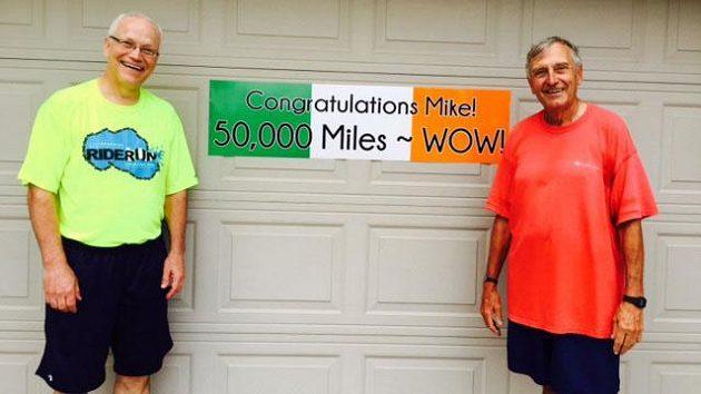 Justin Tolan (vlevo) a Mike Sheehan a společná velká chvíle - 50 000 mil je uběhnuto.