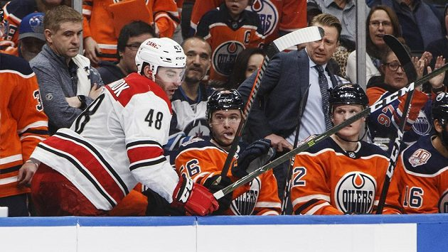 Jordan Martinook (v bílém) z Caroliny skončil po zásahu Zacka Kassiana na střídačce Edmontonu.