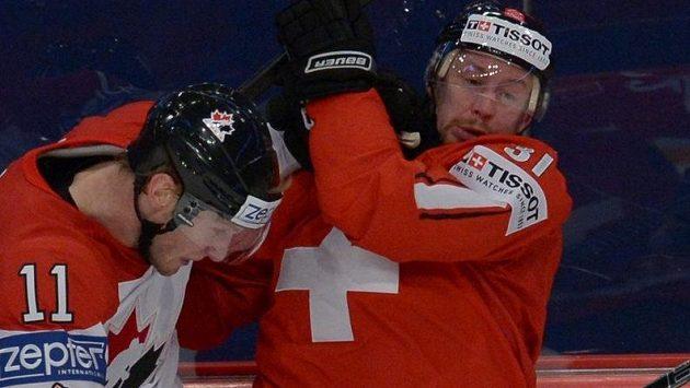 Kapitán švýcarského týmu Mathias Seger (vpravo) v souboji s Kanaďanem Jordanem Staalem.
