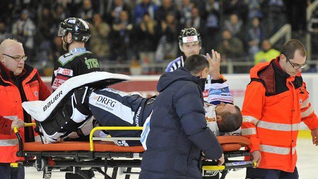 Zraněný brněnský brankář Marek Čiliak zdraví fanoušky, zatímco jej zdravotníci odnášejí z ledu.