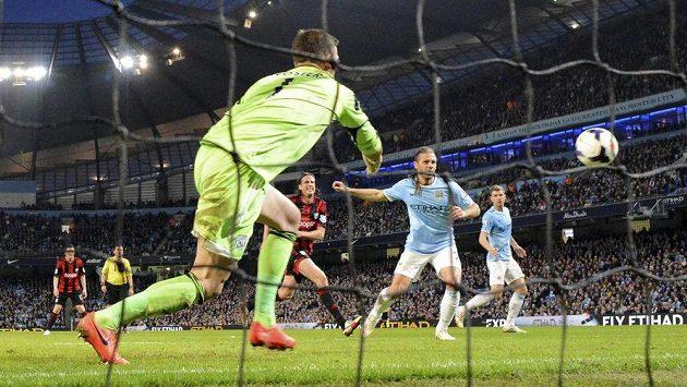 Martin Demichelis z Manchesteru City (v modrém) překonává gólmana WBA Bena Fostera.
