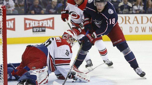 Brankář Caroliny Curtis McElhinney zasahuje proti Pierru-Lucovi Duboisovi v utkání NHL proti Columbusu.
