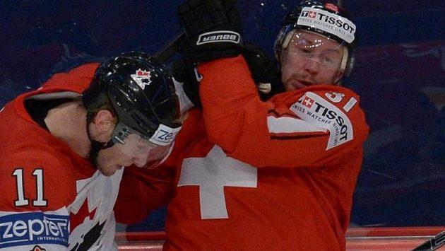 Švýcarský kapitán Mathias Seger (vpravo) v souboji s Kanaďanem Jordanem Staalem.
