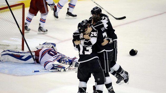 Hráči LA Kings se radují z rozhodující trefy letošního Stanley Cupu z hokejky Aleca Martineze.