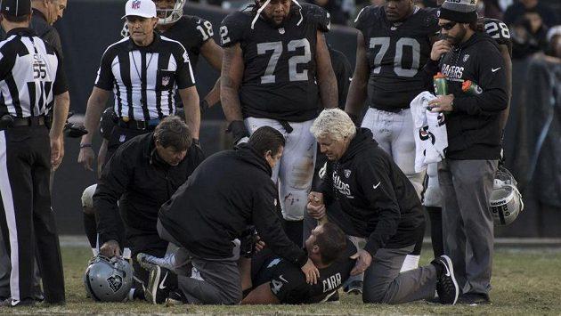 Quarterback Oaklandu Raiders Derek Carr (dole) je ošetřován po tvrdém nárazu.