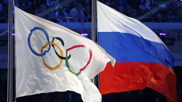 Ruská národní vlajka (vpravo) a vlajka olympijská vlály při zakončení her v Soči.